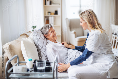 Fotografía  A health visitor examining a sick senior woman lying in bed at home with stethoscope