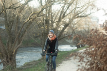 Woman Cycling Along A Footpath By The River, Germany