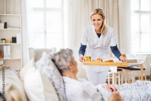 A health visitor bringing breakfast to a sick senior woman lying in bed at home Canvas Print