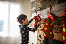 Smiling Boy Hanging A Christmas Stocking On A Fireplace
