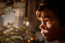 Boy Looking At A Crystal Ornament Hanging On A Christmas Tree