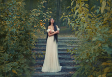 A Princess With Sexually Bare Shoulders Enjoys A Moment Of Silence And Loneliness. Black Long Hair, Golden Wreath, Cream Silk Vintage Dress. Runaway Bride