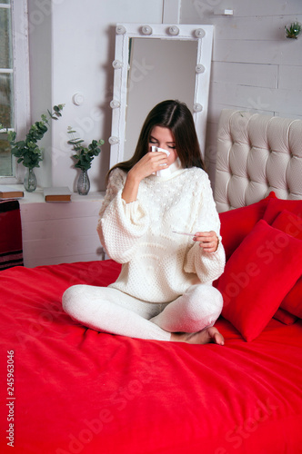 Fotografia  A sick woman is sitting on a bed, holding a handkerchief in her hands, looking at a thermometer