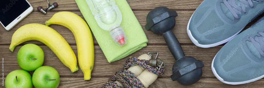 Fototapeta Top view of Healthy lifestyle concept, sport equipments and fresh foods on wood background.  Web Banner. - obraz na płótnie