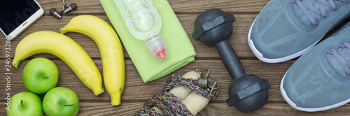Fototapeta Top view of Healthy lifestyle concept, sport equipments and fresh foods on wood background.  Web Banner. obraz
