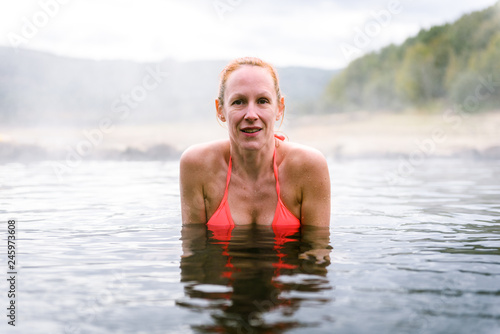 Woman relaxes and enjoys natural hot thermal water roman spa.