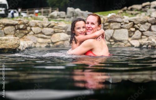 Mother and daughter relaxing in natural thermal water roman spa.