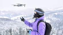 Male Snowboarder In The Violet Jacket And Black Helmet Launching A Flying Drone With A Remote Controller In His Hand On Winter Mountain