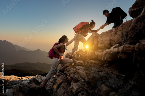 Fototapeta Group of Asia hiking help each other silhouette in mountains with sunlight.. obraz