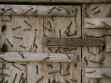 Closeup Detail Of Rustly Nails And Metal Structure Inside Old Wooden Door.