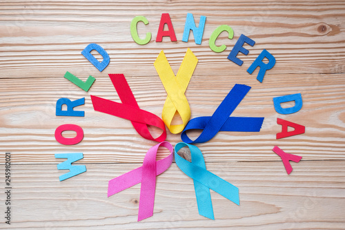 73afad0d64d World cancer day (February 4). colorful awareness ribbons; blue, red,  green, pink and yellow color on wooden background for supporting people  living and ...