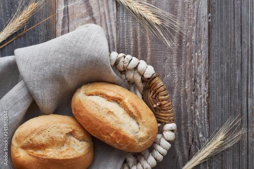 Fototapeta Bread buns in basket on rustic wood with wheat ears obraz