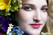 Young Woman's Face With Red Lipstick Surrounded By Colorful Flowers, Close Up.