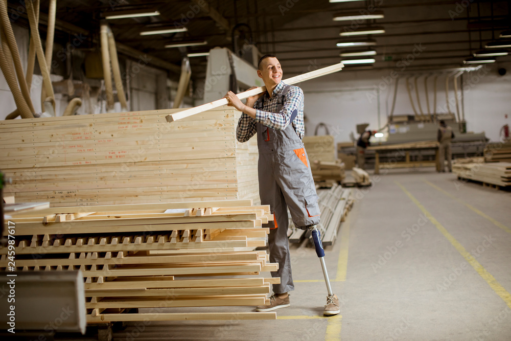 Fototapety, obrazy: Disabled young man with an artificial leg is working at furniture factory