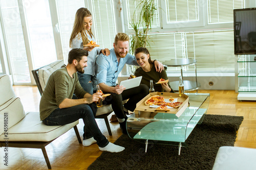 Fototapety, obrazy: Young people eating pizza, drinking cider and watching digital tablet in the room