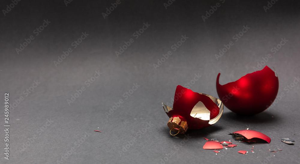 Fototapeta Red Christmas ball broken, dark gray background, closeup view