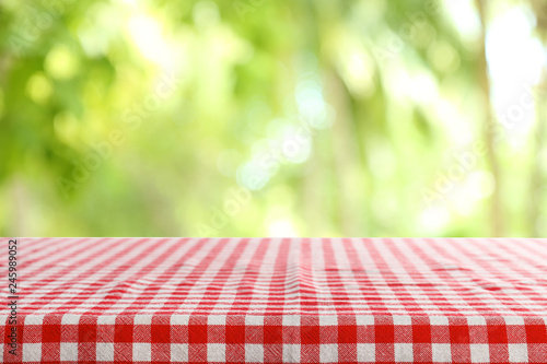 Aluminium Prints Picnic Empty table with checkered red napkin on green blurred background. Space for design