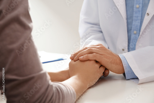 Fotografia  Male doctor comforting woman at table, closeup of hands
