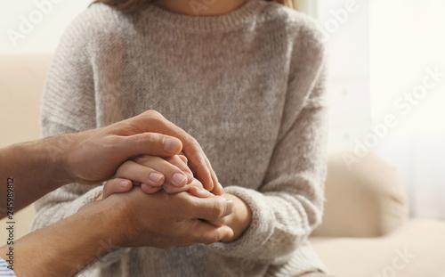 Obraz na płótnie Man comforting woman on light background, closeup of hands