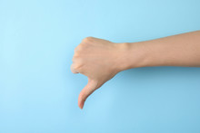 Woman Showing Thumb Down Sign On Color Background, Closeup. Body Language