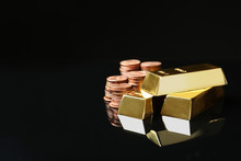Shiny Gold Bars And Coins On Black Background. Space For Text
