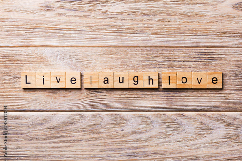 Photo  Live laugh love word written on wood block