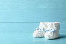 Handmade Baby Booties On Table Against Wooden Background. Space For Text