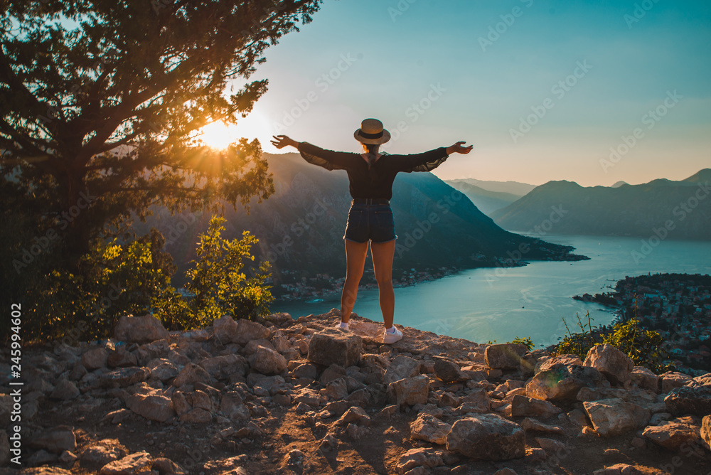 Fototapety, obrazy: woman standing on the top of hill. kotor with sunset on background