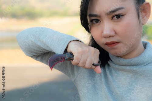 Woman holding bloody knife  karambit in hand on a black background, Social Viole Wallpaper Mural