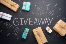 The Inscription Giveaway Written On A Blackboard With Gifts. The Distribution Of Gifts