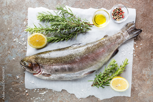 Obraz na płótnie Raw trout fish on paper with rosemary and lemon on a stone table, top view