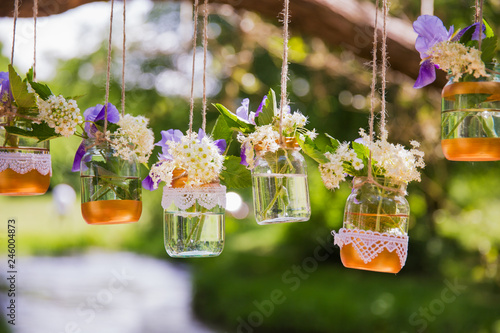 Fotografía  The beautiful flowers in the glasses holding on the cords outdoor