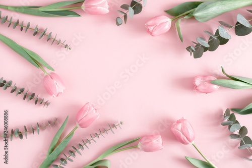 Foto op Canvas Bloemen Flowers composition romantic. Pink flowers tulips, eucalyptus leaves on pastel pink background. Frame made of eucalyptus branches and tulips. Flat lay, top view, copy space