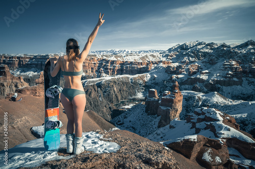 Deurstickers Wintersporten Naked sexy snowboarder girl with snowboard and ski glasses at unusual amazing the Charyn Canyon