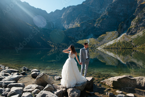 Groom and bride in beautiful white wedding dress standing on the stony shore of the Morskie Oko lake in Poland. Scenic mountain view