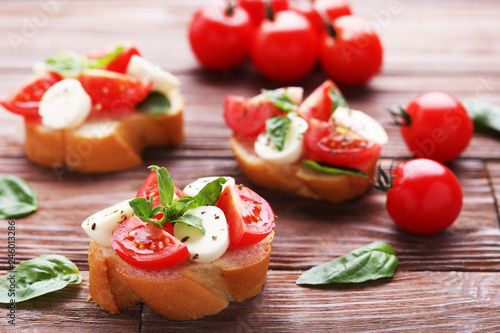 Bruschetta with mozzarella, tomatoes and basil leafs on wooden table Canvas Print