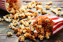 Caramel Popcorn In Paper Bag On Wooden Table