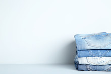Stack Of Folded Jeans On Grey Background