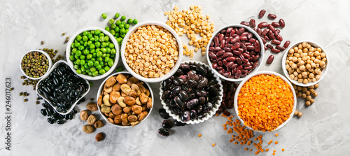 Fototapeta Selection of legumes - beans, lentils, mung, chickpea, pea in white bowls on stone background obraz
