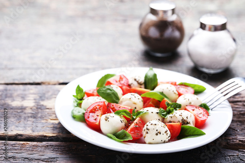 Photo  Mozzarella, tomatoes, basil leafs with salt and pepper on wooden table