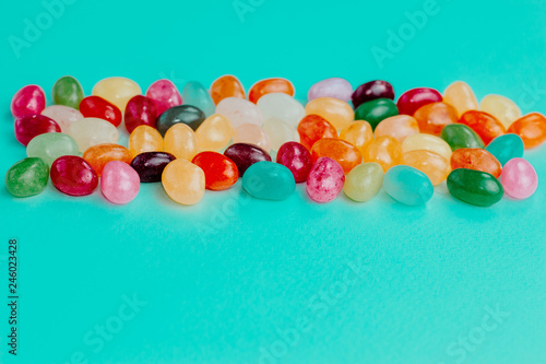 Colorful bean sweet candies on bright turquoise blue background. Easter concept. Close up. Copy space.