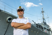 Captain Standing In Dock Before Warship And  Looking Ahead. A Sailor Officer In White Uniform Stands Beside Battleship.