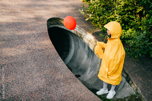 Obraz Portrait of pretty litle girl in big adult oversized yellow raincoat with red balloon in hand standing and sitting against sewage tunnel pipe. Scary movie concept. Funny child posing in summer day. - fototapety do salonu