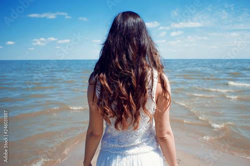 In de dag Bleke violet Young beautiful brunette woman in white dress on the seashore.