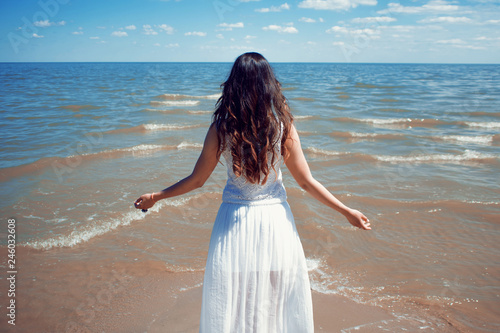 Fotografía Young beautiful brunette woman in white dress on the seashore.