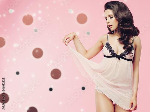 Valokuva  Emotional beautiful brunette girl posing at studio and playfully raises short dress up
