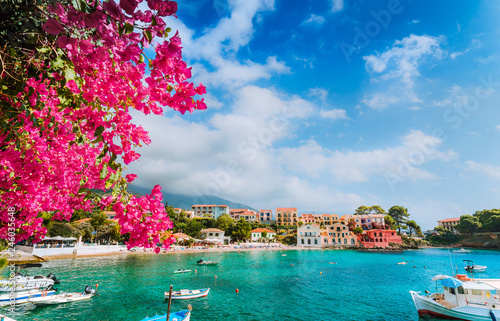 Foto auf AluDibond Himmelblau Beautiful Assos village scenery framed with branch of magenta blossom fuchsia flower. Summer vacation concept