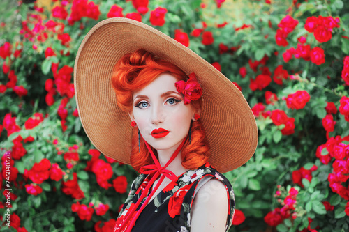 Fotografia  Girl with red lips in rose print dress on summer garden
