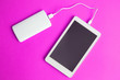canvas print picture - Digital tablet with external battery charger abstract isolated on rose.