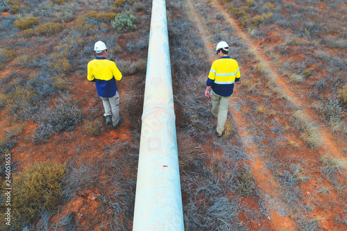 Fototapeta Engineers undertaking a condition assessment of an above ground water pipeline in the Australia outback obraz